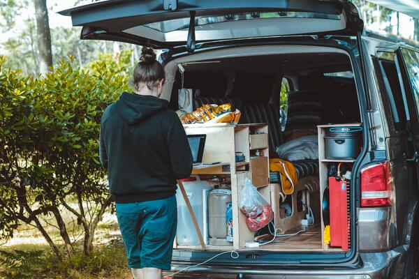 person using laptop behind van | Photo by Brina Blum on Unsplash